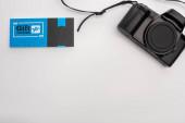 Horní pohled na dárkový poukaz u digitálního fotoaparátu na bílém povrchu s kopírovacím prostorem