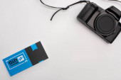 Horní pohled na modrý dárkový poukaz a digitální fotoaparát na bílém pozadí