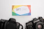 Horní pohled barevné dárkové karty a digitálních fotoaparátů na bílém pozadí