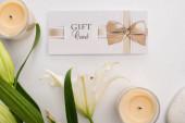 Horní pohled na dárkové karty, lilie a svíčky na bílém pozadí