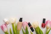 Horní pohled na tulipány s listy a dekorativní kosmetiky na bílém pozadí
