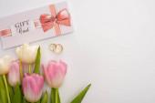Horní pohled na dárkové karty v blízkosti květin a snubních prstenů na bílém pozadí