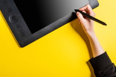 Cropped view of designer holding modern stylus near drawing tablet with blank screen on yellow stock vector