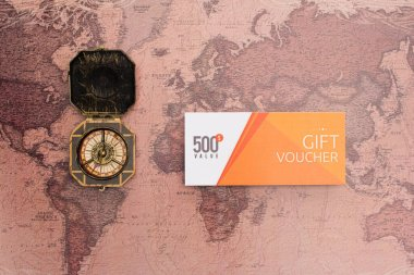 Top view of gift voucher with 500 value lettering and compass on map surface stock vector