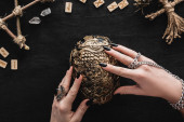 Photo top view of woman touching skull near runes, voodoo doll and crystals on black