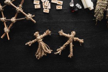 Top view of voodoo dolls, scandinavian runes, pentagram, candles and crystals on black stock vector