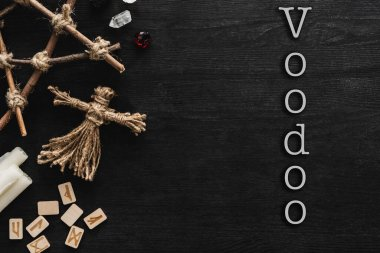 Top view of voodoo dolls, ancient runes, pentagram, candles and crystals near voodoo lettering on black stock vector