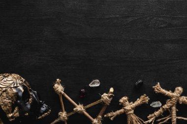 Top view of voodoo dolls, ancient crystals, pentagram and skull on black stock vector
