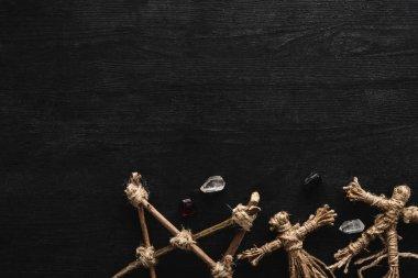 Top view of voodoo dolls, ancient crystals and pentagram on black stock vector