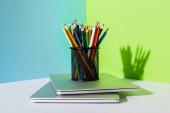 ceruzatartó színes ceruzával modern laptopokon, kék, zöld és fehér háttérrel
