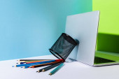 elszórt színes ceruza tartó közelében modern laptop kék, zöld és fehér háttér