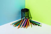 rozptýlené barevné tužky z držáku tužky na modrém, zeleném a bílém pozadí