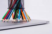 barevné tužky v držáku tužky na moderním notebooku na bílém pozadí