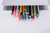 barevné tužky v moderním notebooku na bílém pozadí