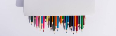 Top view of colored pencils in modern laptop on white background, panoramic shot stock vector