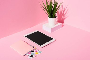 Digital tablet with blank screen, notebooks, plant on pink background stock vector