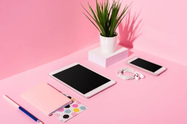 Modern gadgets with blank screens, stationery, earphones and plant on pink background stock vector