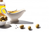 Photo olive oil in bottle and sauce boat near green olives and black pepper on white background