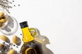 vrchní pohled na olivový olej v láhvi v blízkosti zelených oliv v misce, bylina a černý pepř na bílém pozadí