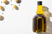 Photo top view of olive oil in bottle near green olives and black pepper on white background