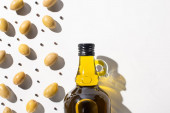top view of olive oil in bottle near green olives and black pepper on white background with shadow