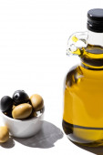 olive oil in bottle near green and black olives in bowl on white background