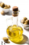 selective focus of olive oil in jar near green olives and black pepper on white background