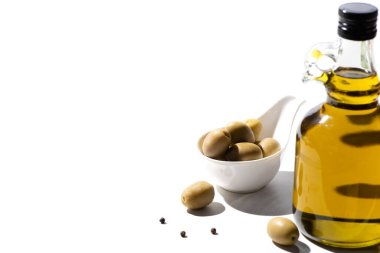 Olive oil in bottle near green olives and black pepper on white background stock vector