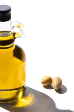 Olive oil in bottle near green olives on white background stock vector