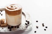 vynikající dalgona káva ve skle v blízkosti kávových zrn, hnědý cukr na stříbrném podnose na bílém pozadí