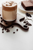 Photo selective focus of delicious Dalgona coffee in glass on wooden cutting board near coffee beans, chocolate and spoon on white background