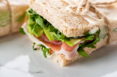 close up view of fresh green sandwich with jamon on marble white surface
