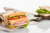 friss, ízletes szendvics szeletelt kolbásszal és salátával szalvétán fehér felületen
