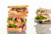 selective focus of fresh sandwiches with arugula and meat on white surface