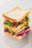 fresh green sandwiches with meat on marble white surface