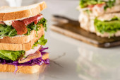 selective focus of fresh sandwiches with meat on marble white surface