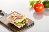 selective focus of fresh green sandwich with avocado and prosciutto on wooden cutting board on white marble surface