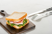 selective focus of fresh sandwich with arugula and prosciutto on wooden cutting board near cutlery on white marble surface