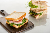 selective focus of fresh green sandwich with prosciutto on wooden cutting board on white marble surface