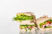 fresh green sandwiches with avocado and meat on white surface