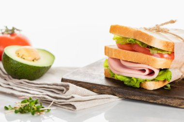 Fresh delicious sandwich with sliced sausage and lettuce on wooden cutting board near napkin and avocado on white surface stock vector