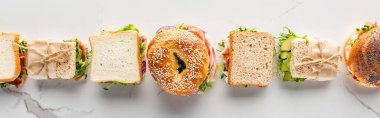 Flat lay with fresh sandwiches and bagels on marble white surface, panoramic shot stock vector