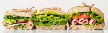 Fresh green sandwiches with avocado and meat on white surface, panoramic shot stock vector
