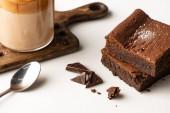 finom brownie darab közelében fa vágódeszka kávé és kanál fehér háttér