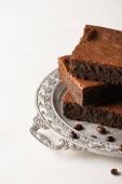 vynikající kousky brownie podávané s kávovými zrny na stříbrném podnose na bílém pozadí