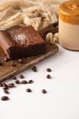 vynikající brownie kus na dřevěné řezací desce s kávovými zrny, kávou a látkou na bílém pozadí