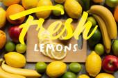vrchní pohled na chutné barevné ovoce a dřevěnou řezací desku s citronovými plátky, čerstvé citrony ilustrace