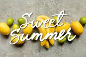 pohled shora na barevné banány, citrony a citrony na šedém betonovém povrchu, sladká letní ilustrace