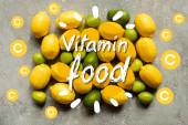 horní pohled na barevné avokádo, citrony a citrony na šedém betonovém povrchu, vitamin potravin ilustrace