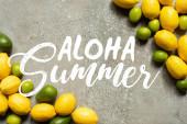 pohled na barevné avokádo, citrony a citrony na šedém betonovém povrchu, letní ilustrace aloha